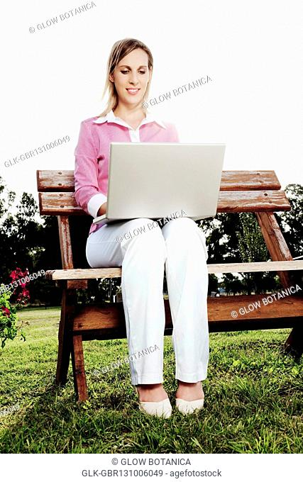 Businesswoman working on a laptop on a bench