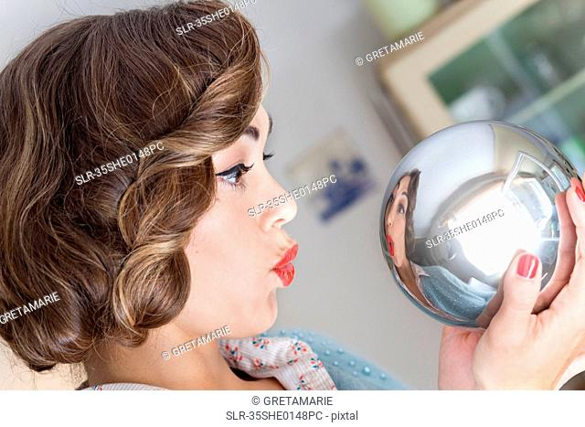 Woman admiring herself in mirrored ball