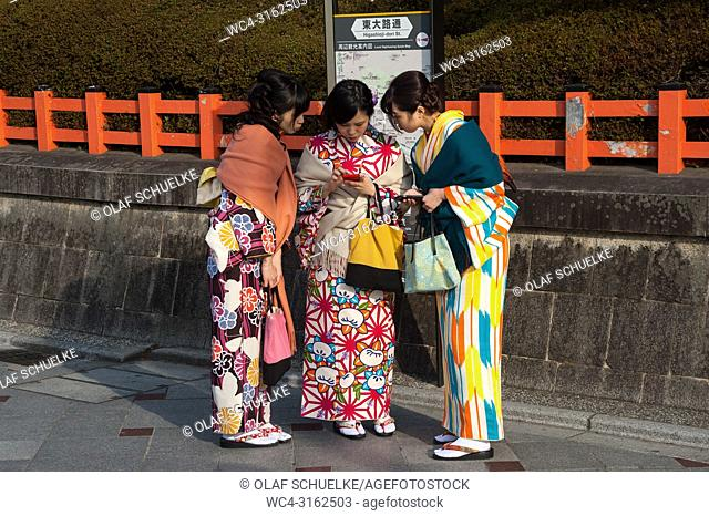 23. 12. 2017, Kyoto, Japan, Asia - Three young women wearing a traditional kimono are seen standing at the roadside in front of Maruyama Park