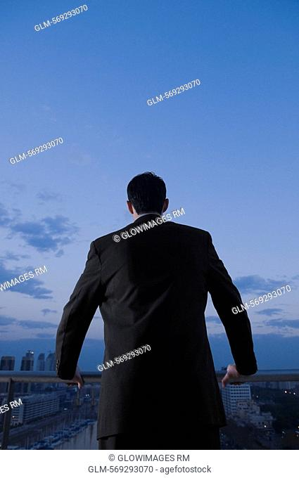 Rear view of a businessman holding a railing