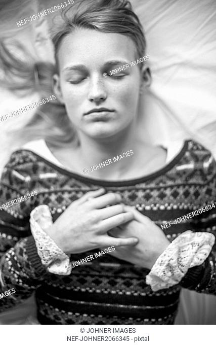 Young woman sleeping on bed with hands clasped
