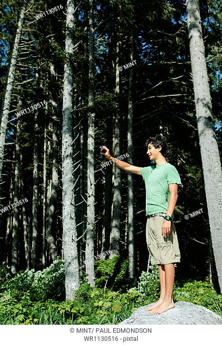 A young boy standing in the forest holding a smart phone up to take a selfy or a photograph, in Olympic national park