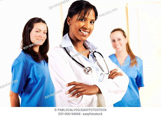 Portrait of a smart young female doctor standing in front of his team and smiling