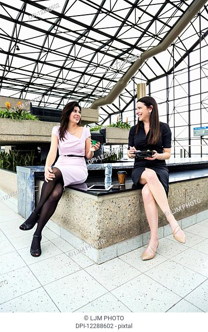 Two business women having lunch together in the atrium of an office building; Edmonton, Alberta, Canada