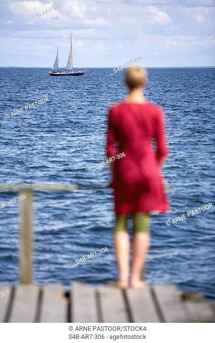 Woman standing on a jetty looking to the sea, Schleswig-Holstein, Germany
