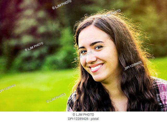 Portrait of a young woman outdoors at sunset; Sherwood Park, Alberta, Canada