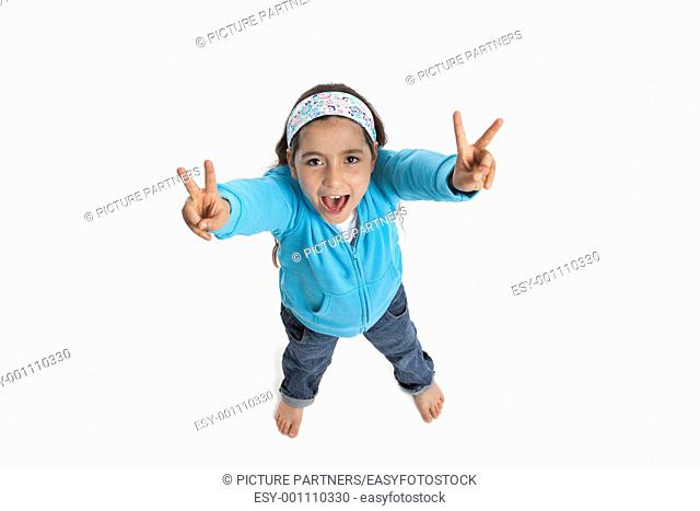 Cool eight year old girl yelling and making a V sign on white background