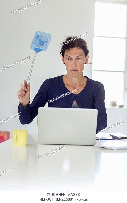 Woman sitting in front of laptop and holding fly swatter