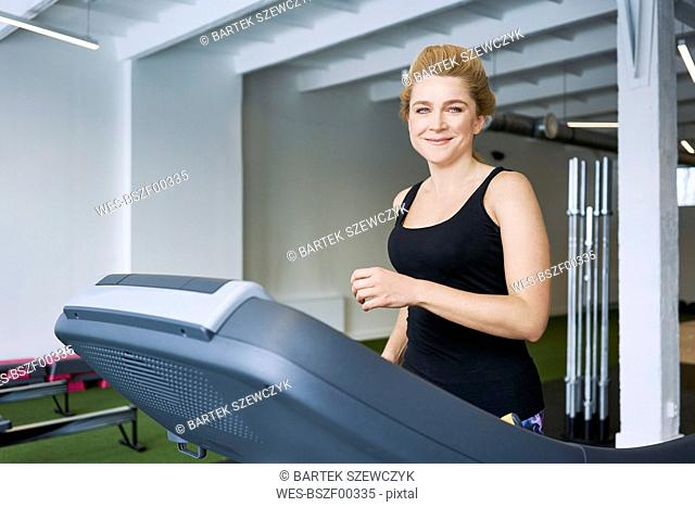 Portrait of smiling woman on treadmill at gym
