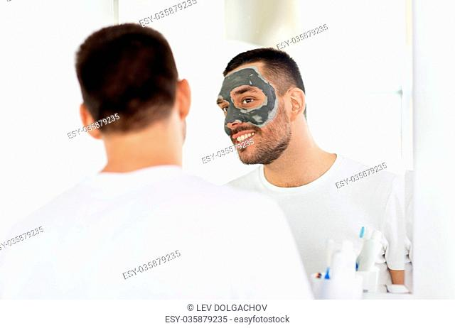 grooming, skin care and people concept - young man with clay mask on face and looking to mirror at home bathroom