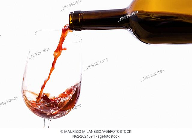 Wine poured from a bottle in a wine glass, on a white background