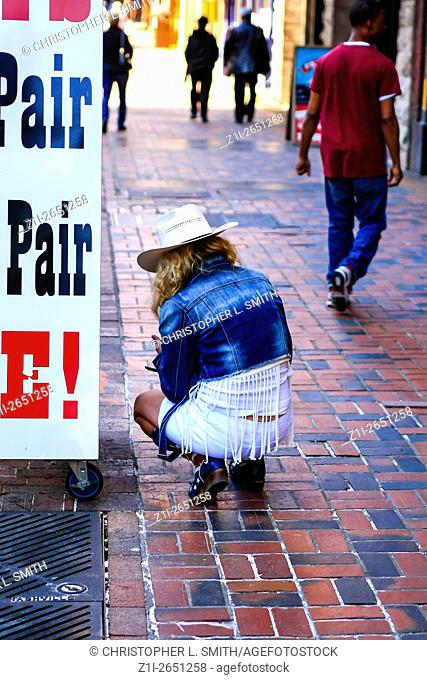 Cowgirl waitress on her way to work in her boots, stetson and tassled skirt in Nashville