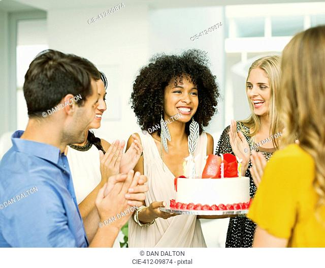 Friends clapping around woman with birthday cake