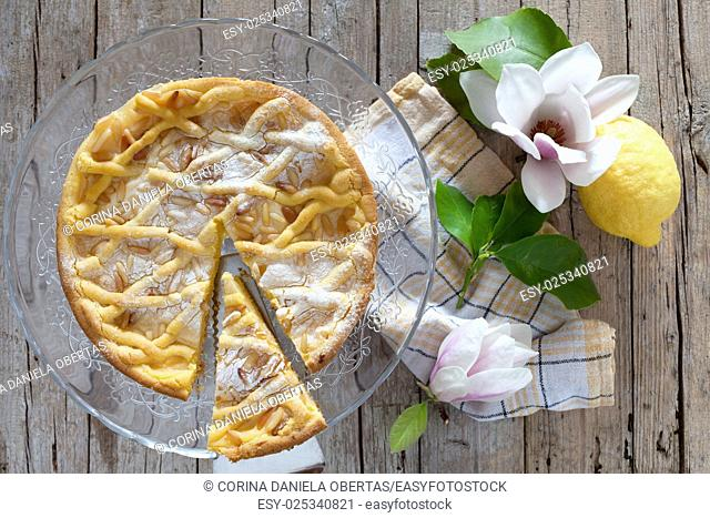 Slice of grandmas cake, typical cake from Tuscany, Italy, made with shortbread pastry, ricotta cheese and pine nuts