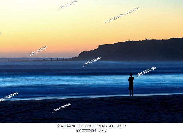 Man on the beach with surf, Opunake, Taranaki Region, New Zealand
