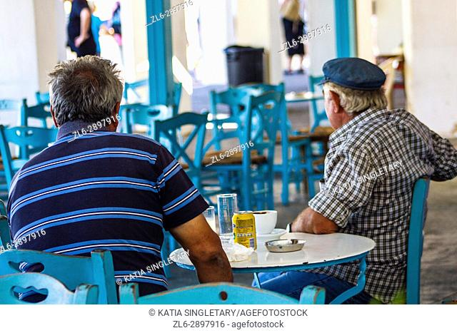 Street life scene of two caucasian gentlemen in their mid 50's sitting at an outdoor cafe smoking a cigarette and enjoying their drink, in Oia, Santorini