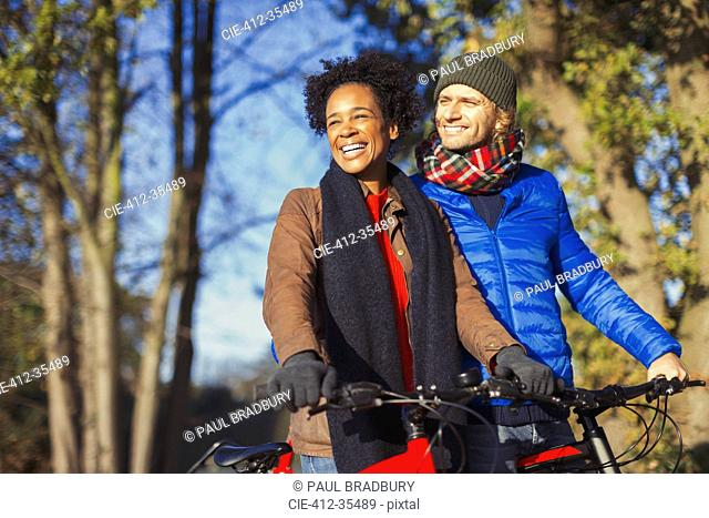 Smiling couple bike riding in sunny autumn park