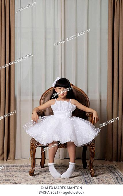 Young girl wearing white dress sitting in nice chair smiling