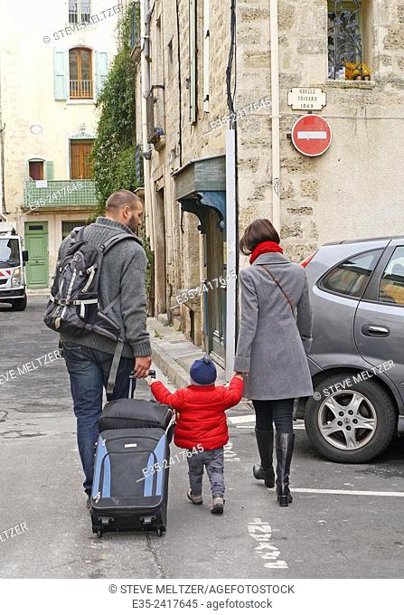 Parents help their child cross the street