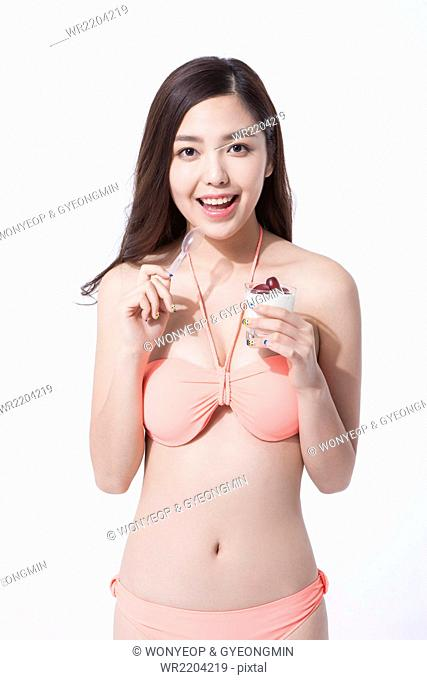 Woman with long hair in bikini holding a cup of yogurt with a spoon and staring forward with a smile