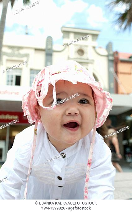 Ten month old girl with pink hat smiling