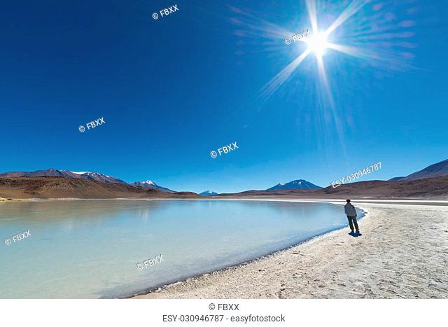 "Tourist walking beside """"Laguna Canapa"""", a salty lake on the way to the famous Uyuni Salt Flat, among the most important travel destination in Bolivia"