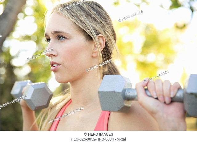Woman using weights for outdoor workout