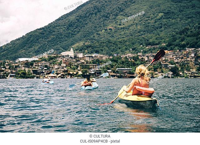 Young adult friends kayaking on Lake Atitlan, Guatemala