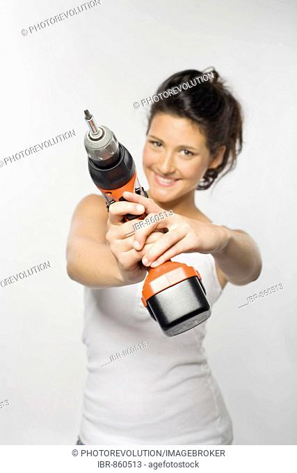 Young woman smiling while holding an electric drill towards the camera