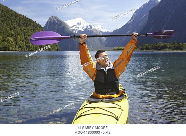 Man hoisting oar of kayak over head in mountain lake