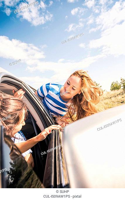 Two female friends leaning out of vehicle window