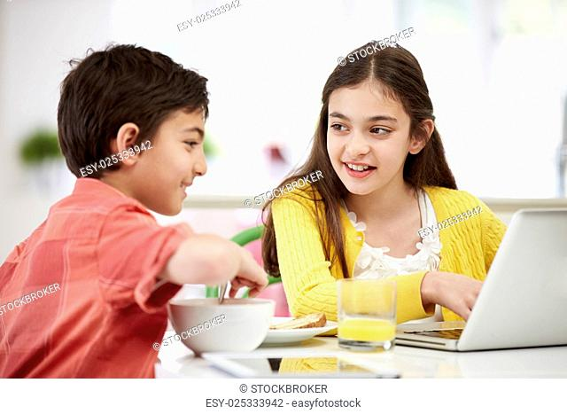 Children With Digital Tablet And Laptop At Breakfast