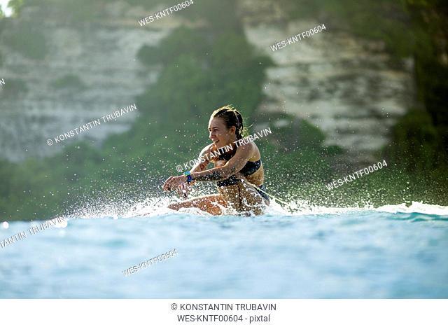Indonesia, Bali, woman sitting on surfboard in the sea