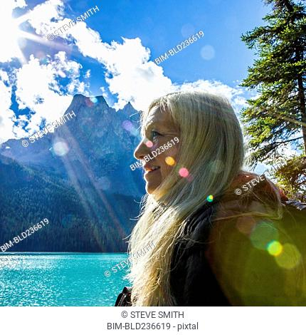 Sunbeams on face of Caucasian woman at mountain lake