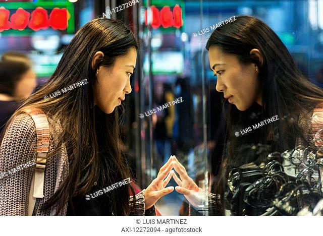A young woman and her reflection in the glass peering into a shop window, Kowloon; Hong Kong, China