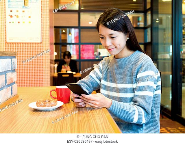 Woman using cellphone and having breakfast