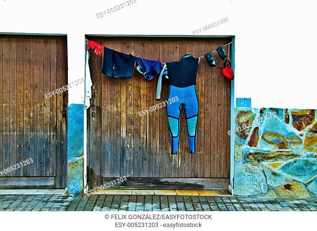 Neoprene wetsuit, drying in a clothes line in Cudillero, Asturias, Spain