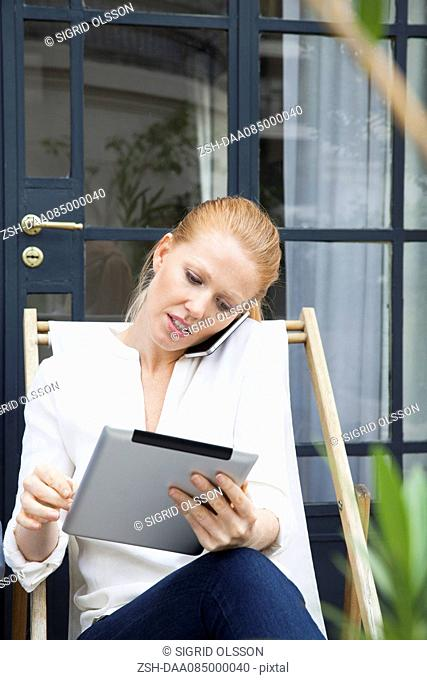 Woman using digital tablet while making phone call