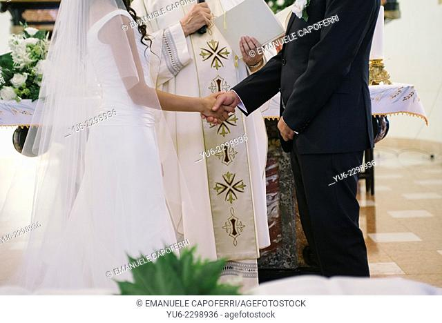 Spouses in front of the priest join hands
