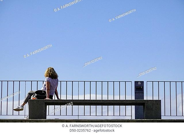 Funchal, Madeira, Portugal A woman sitting by the ocean on a bench