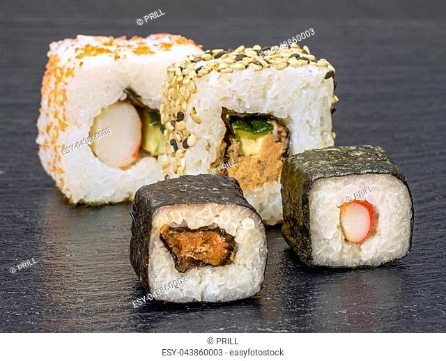 various sushi dishes on dark grey stone surface