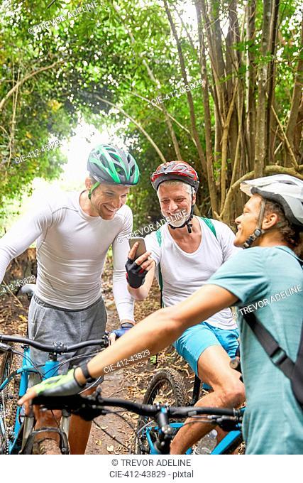 Male friends mountain biking, using smart phone in woods