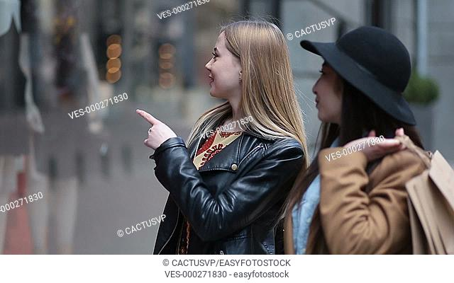 Beautiful girlfriends pointing at store window