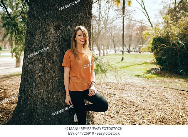 Young smiling blonde woman supported on a tree with black jeans