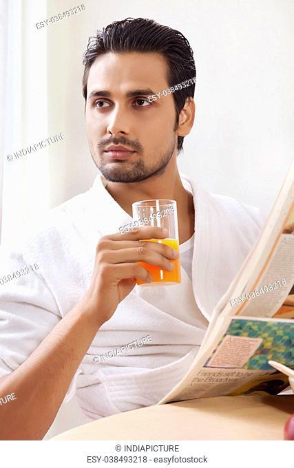 Portrait of man drinking juice holding newspaper