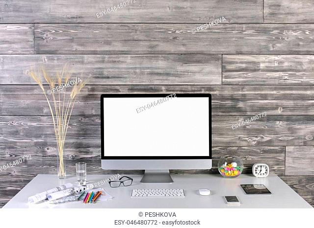 Creative hipster desktop with blank white computer monitor, keyboard, mouse, tablet, smartphone, decorative, stationery and other items on wooden plank wall...