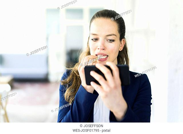 Businesswoman holding cell phone applying lipstick