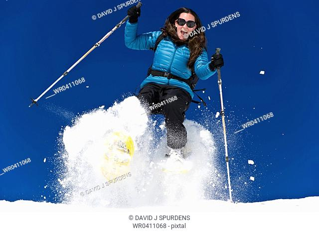 A woman snowshoeing and having fun in fresh powder snow