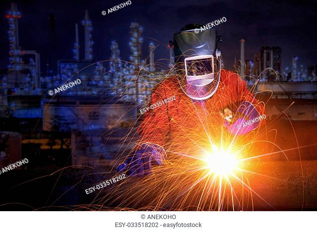 worker with protective mask welding metal and sparks in oil refinary plant