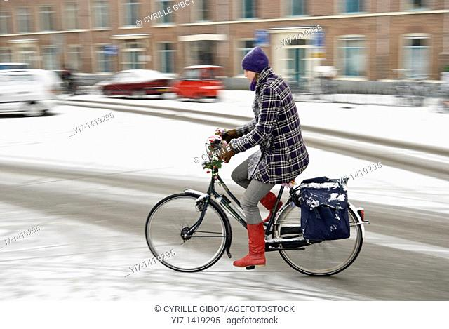 A woman on a bicycle enters a slippery turn during snowfall, Amsterdam, the Netherlands